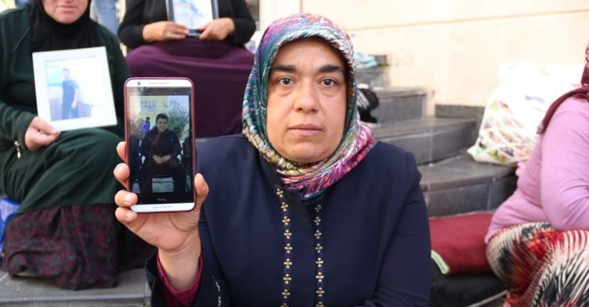 PKK terrorist Cafer Ceylan's mother Hatice Ceylan poses with his picture in front of the HDP HQ in Diyarbak?r during protests (AA File Photo)