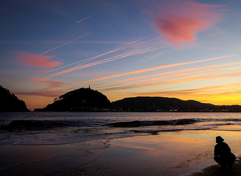 A man looks as the sun rises over the beach of Ondarreta in San Sebastian, in the northeren region of the Basque Country, Spain, 24 October 2017 (EPA Photo)