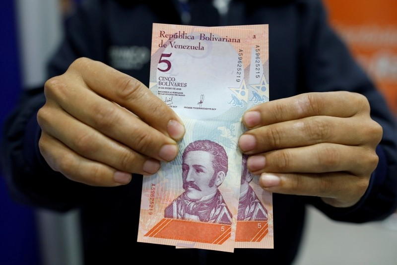 A man shows the new five Bolivar Soberano (Sovereign Bolivar) bills, after he withdrew them from an automated teller machine (ATM) at a Mercantil bank branch in Caracas, Venezuela August 20, 2018. (REUTERS Photo)