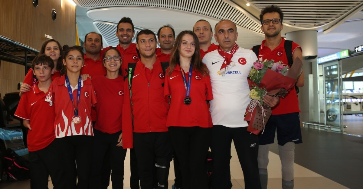 Su00fcmeyye Boyacu0131, third from  right, and Sevilay u00d6ztu00fcrk, third from left, pose with their medals at Istanbul Airport after they returned from London, Sept. 16, 2019.
