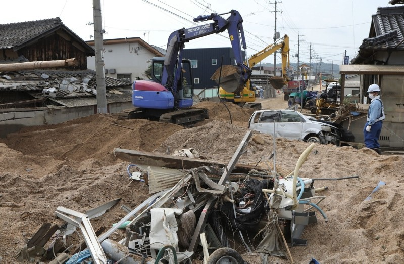 Workers remove sediment that flowed into the residential area of Mabicho in Kurashiki, Okayama prefecture on July 12, 2018. (AFP Photo)