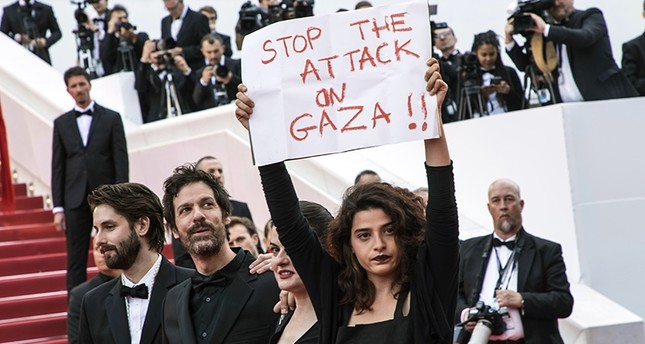 Lebanese actress Manal Issa, from My Favorite Fabric, right, holds a sign that reads Stop the Attack on Gaza at the premiere of the film Solo: A Star Wars Story at the 71st international film festival, Cannes, France, May 15, 2018. (AP Photo)
