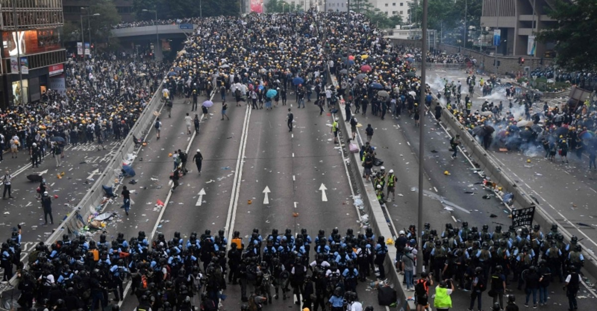 Protesters face off with police after they fired tear gas during a rally against a controversial extradition law proposal outside the government headquarters in Hong Kong on June 12, 2019. (AFP Photo)