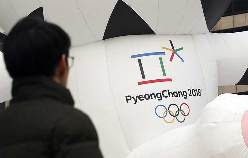 A man walks by the official emblem of the 2018 Pyeongchang Olympic Winter Games, in downtown Seoul, South Korea. (AP Photo)