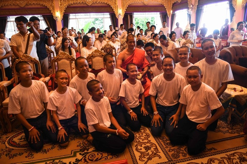 Thai coach Ekkapol Chantawong (C) and all 12 members of the ,Wild Boars, football team pose for a photo together after a ceremony to mark the end of the 11 players' retreat as novice Buddhist monks. (AFP Photo)
