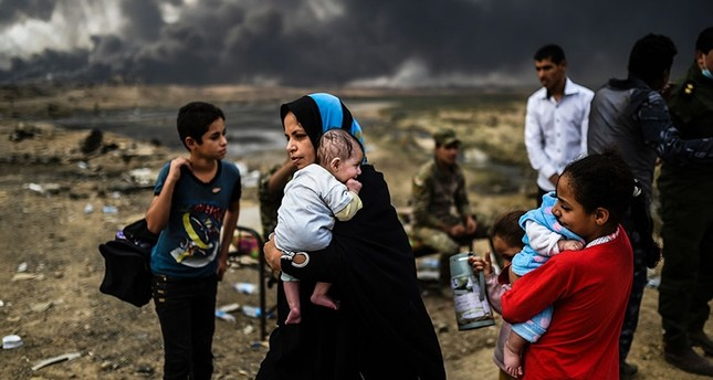 Iraqi families, who were displaced by the ongoing operation by Iraqi forces against Daesh terrorists  to retake the city of Mosul, are seen gathering on an area near Qayyarah on October 24, 2016. (AFP Photo)