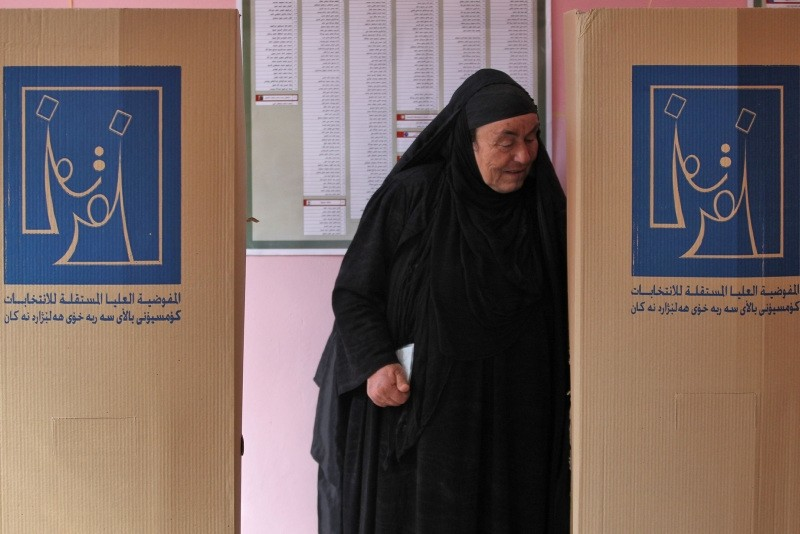 An Iraqi woman walks out of a voting booth in the Wadi Hajar district of Mosul, Iraq, May 12.