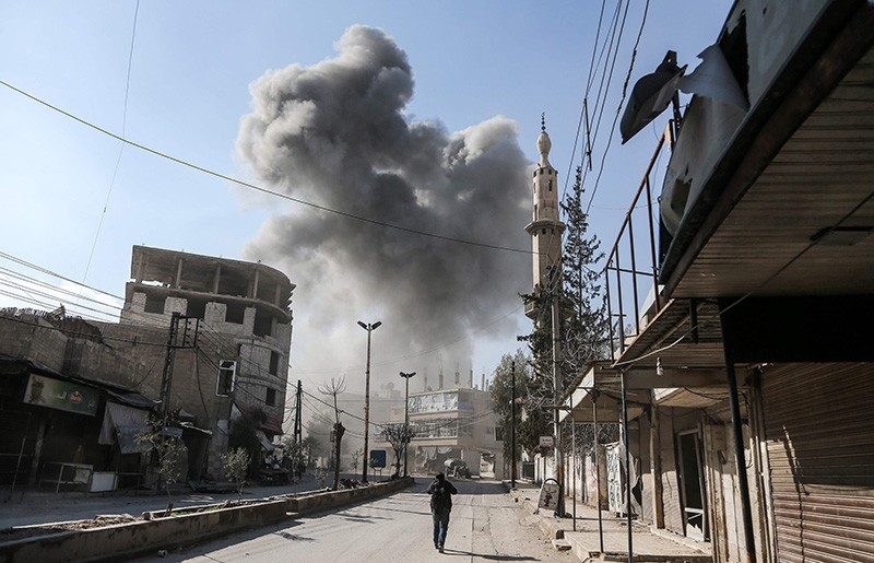 A picture taken on February 21, 2018 shows a smoke plume rising following a reported regime air strike in the opposition-held enclave of Hamouria in the Eastern Ghouta near Damascus. (AFP Photo)