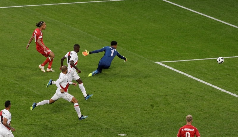 Denmark's Yussuf Yurary Poulsen scores his side's opening goal past Peru goalkeeper Pedro Gallese during the group C match between Peru and Denmark at the 2018 soccer World Cup in the Mordovia Arena in Saransk, Russia, Saturday, June 16, 2018. (AP)