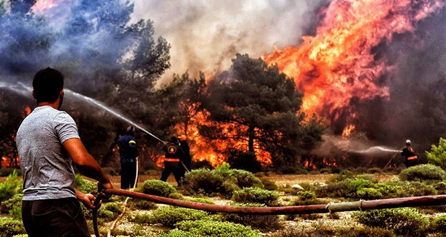 Firefighters and volunteers try to extinguish a wildfire raging in Verori, near Loutraki city, Peloponnese, southern Greece, July 24, 2018. (EPA Photo)