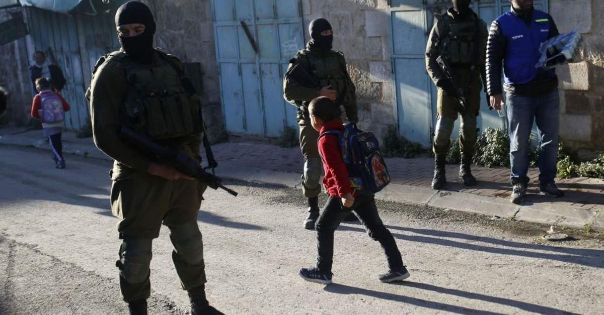 Palestinian children walk past Israeli soldiers on their way to school, Hebron, Feb. 12, 2019. (AP Photo)
