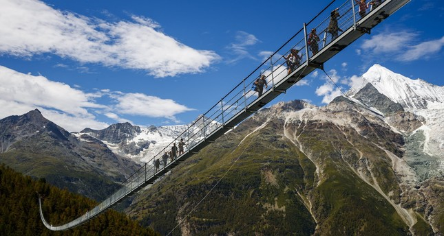 People walk on the 'Europabruecke' bridge, the world's longest pedestrian suspension bridge with a length of 494m, after the official inauguration of the construction in Switzerland, 29 July 2017. (EPA Photo)