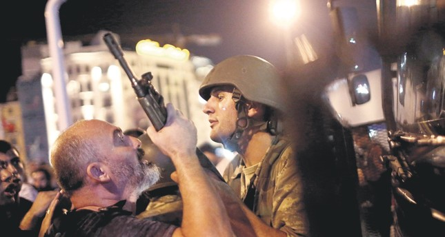 A civilian tries to take the rifle of a soldier at Istanbul's Taksim Square. This act of resistance was just one of the many that became a symbol of the people's defense of democracy against the coup attempt.