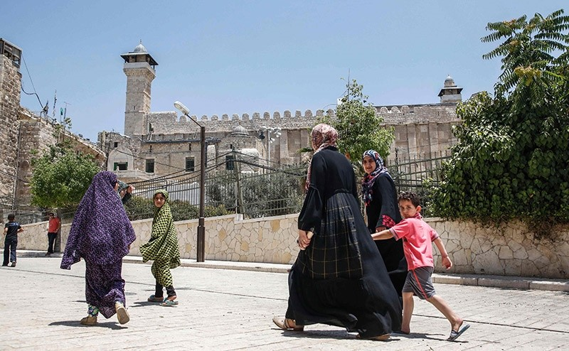 Palestinians walking by outside the Cave of the Patriarchs, also known as the Ibrahimi Mosque, which is a holy shrine for Jews and Muslims, from the Palestinian side in the heart of the divided city of Hebron in the West Bank. (AFP Photo)