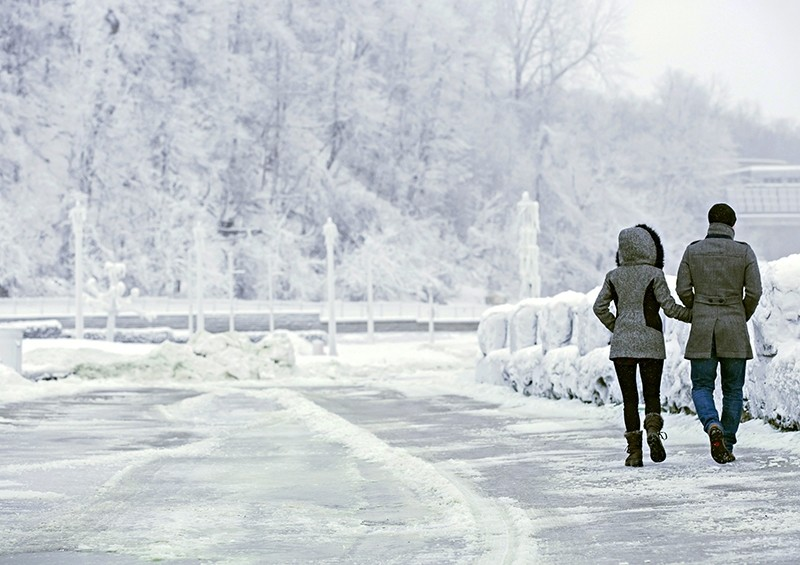 A couple walks near the brink of the Horseshoe Falls in Niagara Falls, Ontario, as cold weather continues through much of the province on Friday, Dec. 29, 2017.