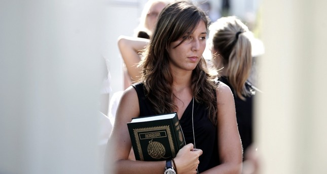 A  woman holds a copy of the Koran after a meeting with Libyan leader Moammar Gadhafi, at the Libyan Academy near the Libyan ambassador's residence in Rome, Sunday, Aug. 29, 2010. AP Photo
