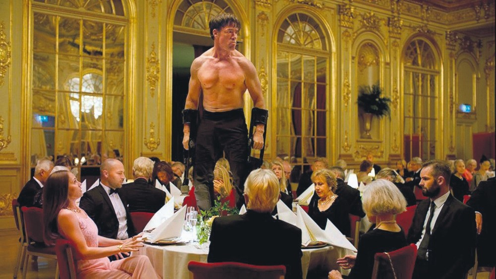 A performance artist acting like an ape, selected to entertain the art-savvy, elegantly dressed public sitting in a very ornate dining hall, tests the boundaries of what the polite audience will endure in order not to break the totem of modern art.