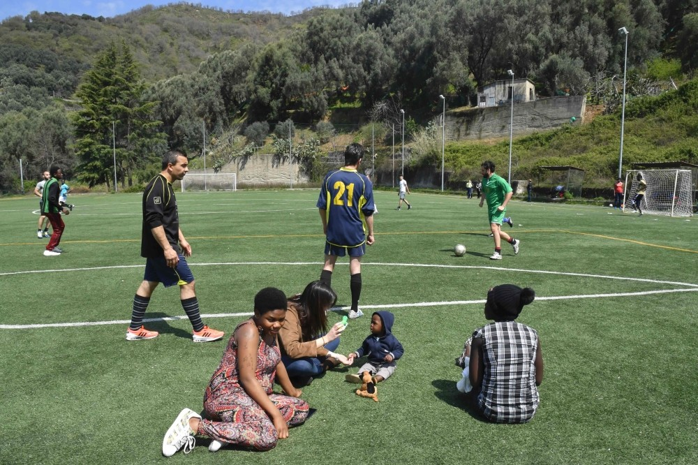 Women migrants Eunice (L) from Nigeria and Hawa (R) from Gambia relax along the pitch as migrants play football with a local team in Santu2019 Alessio in Aspromonte, a small village of 330 inhabitants in Calabria.