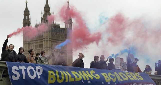 Demonstrators hold flares and a banner over Westminster Bridge in front of the Parliament buildings in London, Nov. 28.