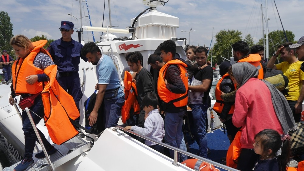 Soldiers accompany intercepted immigrants to shore.