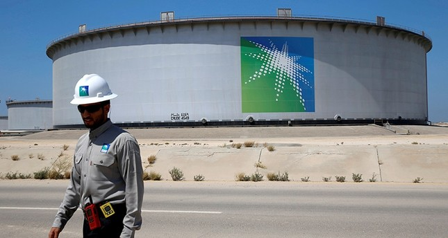 An Aramco employee walks near an oil tank at Saudi Aramco's Ras Tanura oil refinery and oil terminal in Saudi Arabia May 21, 2018. (Reuters Photo)