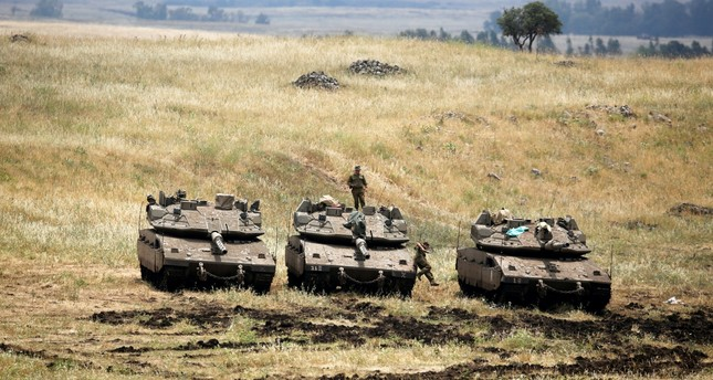 An Israeli soldier stands on a tank near the border with Syria in the Israeli-occupied Golan Heights, May 9.