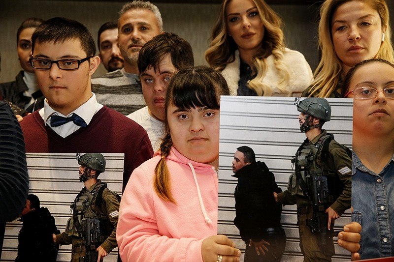 Members of the Turkey-based International Down Syndrome Federation (UDF) show a picture of 14-year-old Palestinian Muhammed et-Tavil who was taken into custody by Israeli soldiers. (AA Photo)