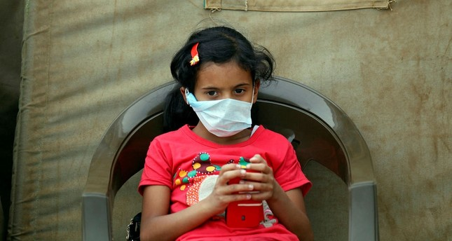 A Yemeni child suspected of being infected with cholera sits outside a makeshift hospital in Sanaa on June 5.