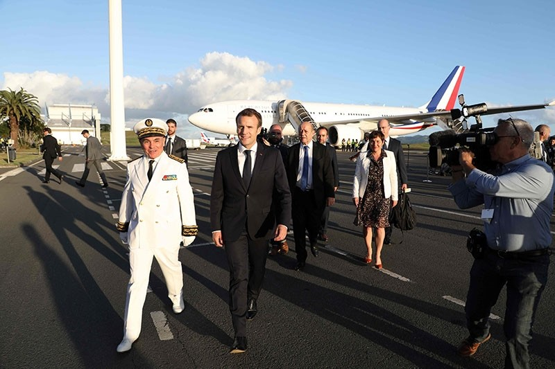 French President Emmanuel Macron (C) walks with officials including Foreign Affairs Minister Jean-Yves Le Drian (C/R) and Overseas Minister Annick Girardin (R) as he disembarks from his aircraft on arrival in Noumea on May 3, 2018. (AFP Photo)