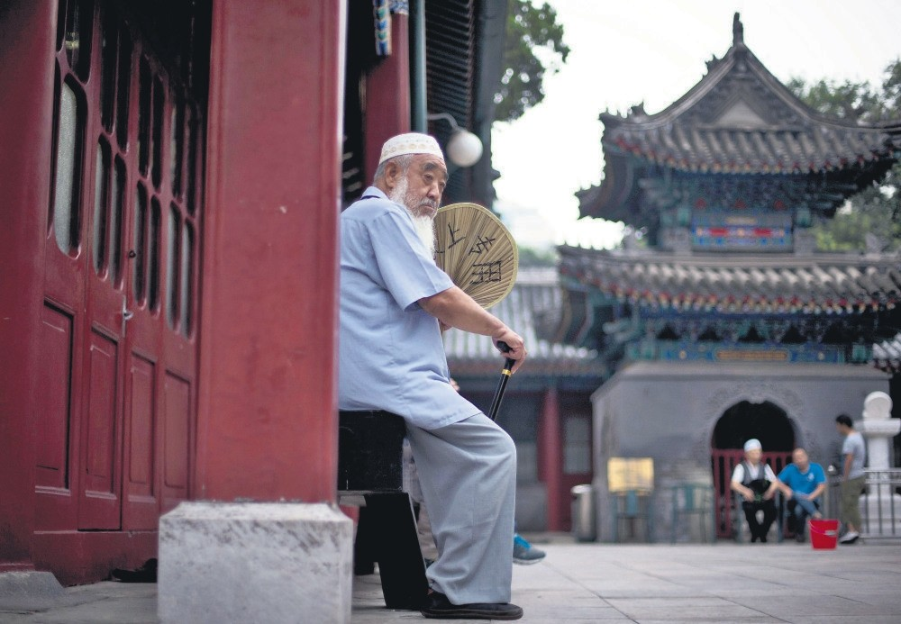 A Muslim man fans himself as he waits for the time to break his fast during the Muslim holy month of Ramadan at the Niujie mosque, the oldest and largest mosque in Beijing, China,  July 2, 2014.