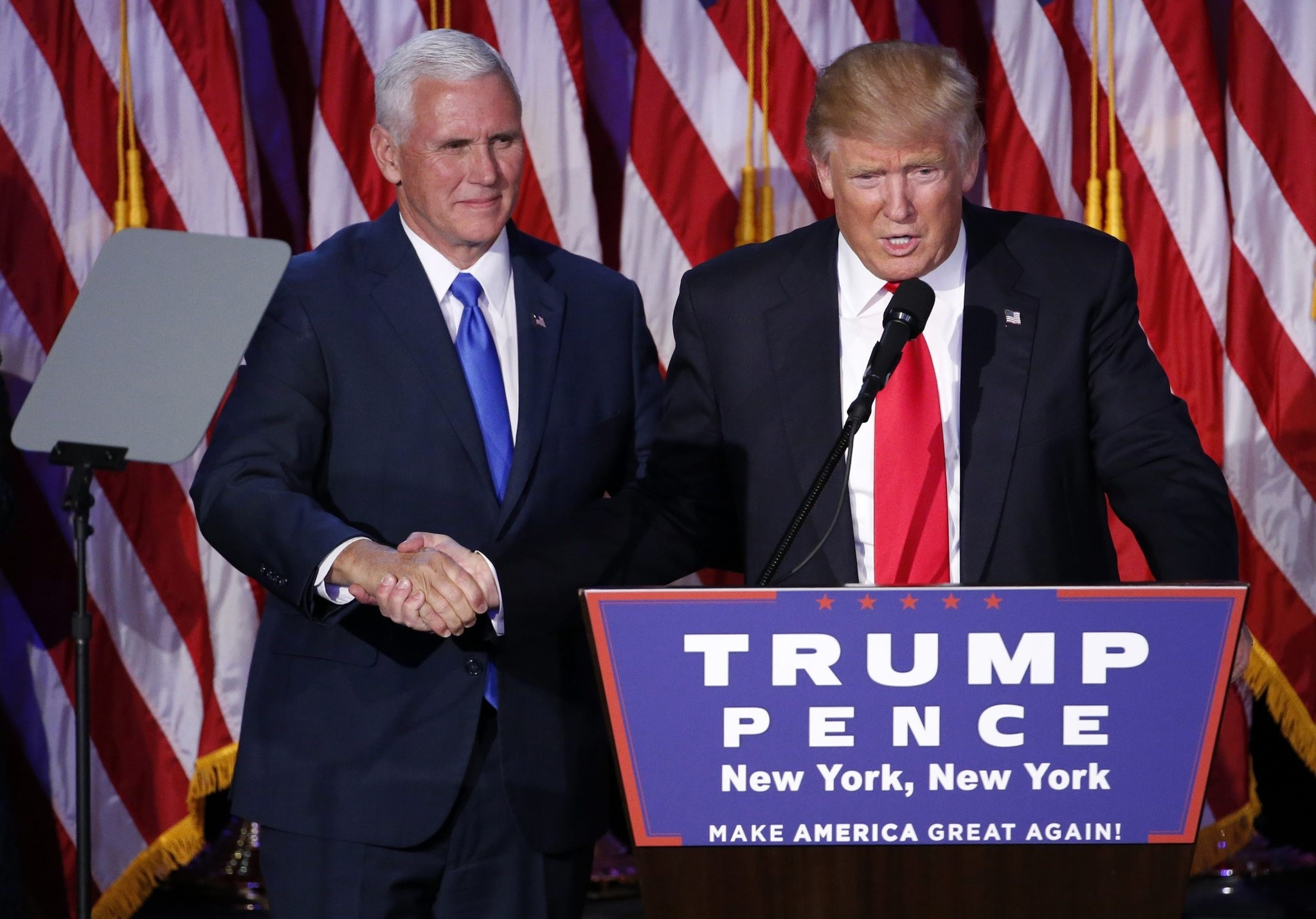 Then U.S. Republican presidential nominee Donald Trump shakes hands with running mate Mike Pence as he delivers a speech while the presidential votes continue to be counted, New York, Nov. 8, 2016.
