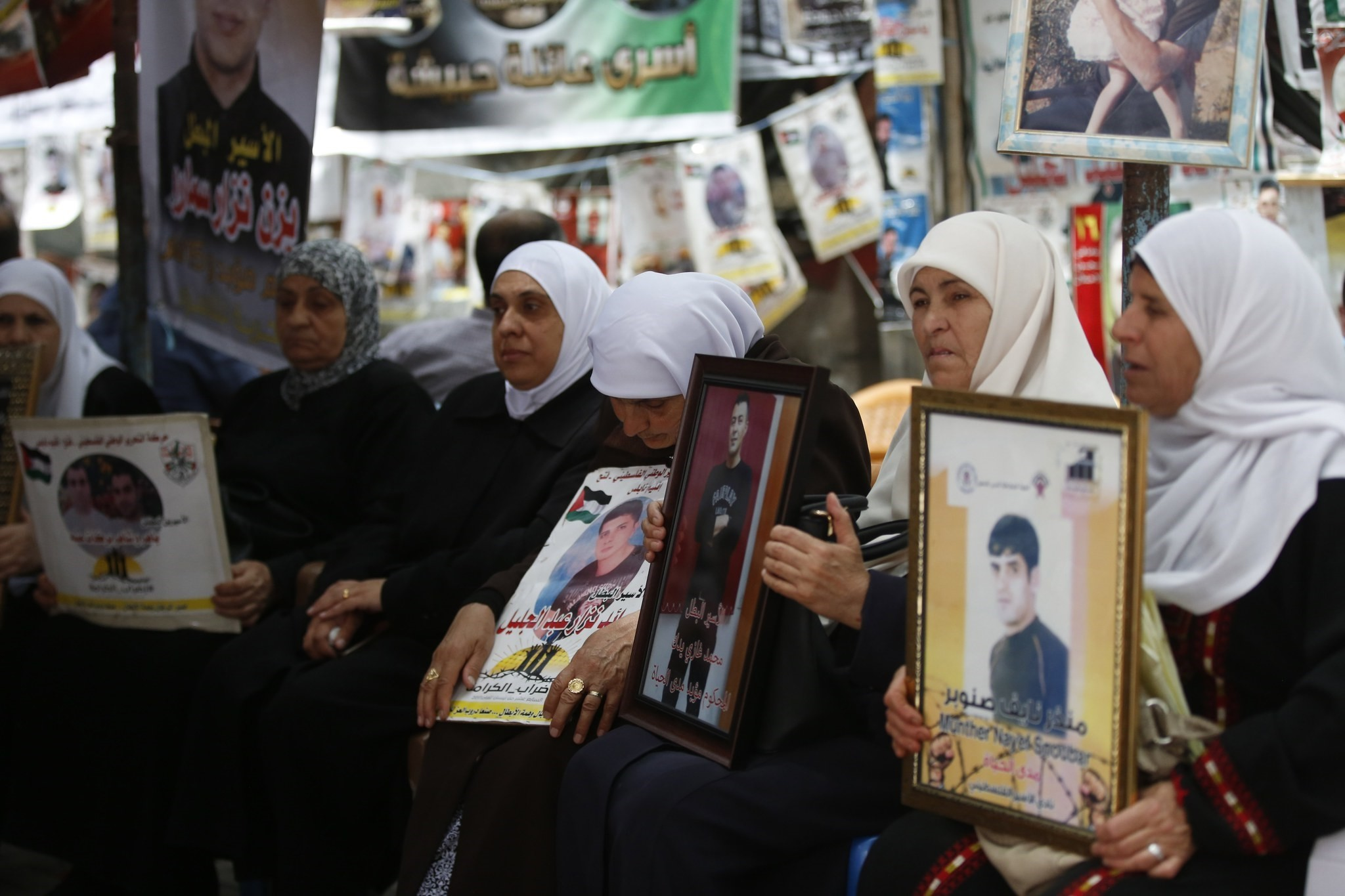 Palestinian mothers hold pictures of their sons held in Israeli jail during a protest in solidarity with prisoners on hunger strike in Israeli jails, in Nablus, 14 May 2017. (EPA Photo)