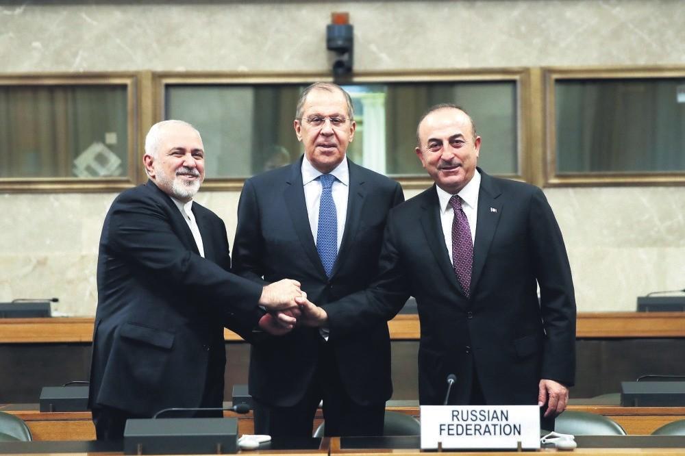 Iranian FM Mohammad Javad Zarif (L), Russian FM Sergei Lavrov (C), and FM Mevlu00fct u00c7avuu015fou011flu (R) shake hands after a joint statement following consultations on Syria, at the European headquarters of the U.N. in Geneva, Switzerland, Dec. 18.