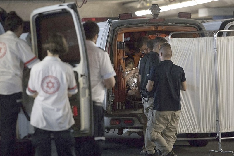 Israeli medical personnel from the Shaare Zedek Hospital in Jerusalem unload a wounded Israeli from an ambulance car, July 21, 2017, after a stabbing attack in the settlement of Halamish, north of Ramallah, West Bank. (EPA Photo)