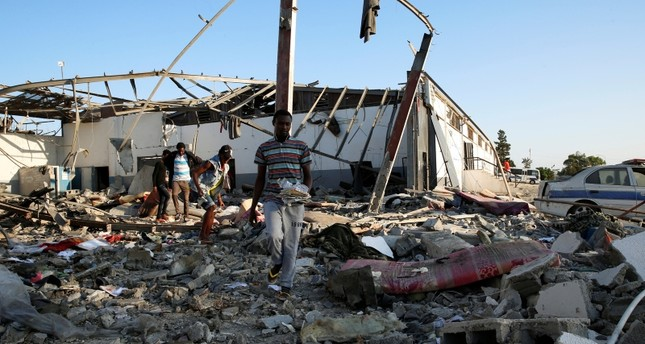 Migrants carry the remains of their belongings from among rubble at a detention center for mainly African migrants that was hit by an airstrike in the Tajoura suburb of the Libyan capital of Tripoli, Libya, July 3, 2019. (Reuters Photo)