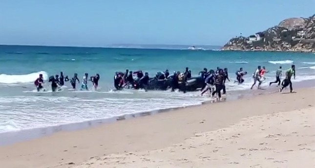 Migrants scatter as a rubber dinghy lands on the beach at Cadiz, southern Spain, Aug. 9.