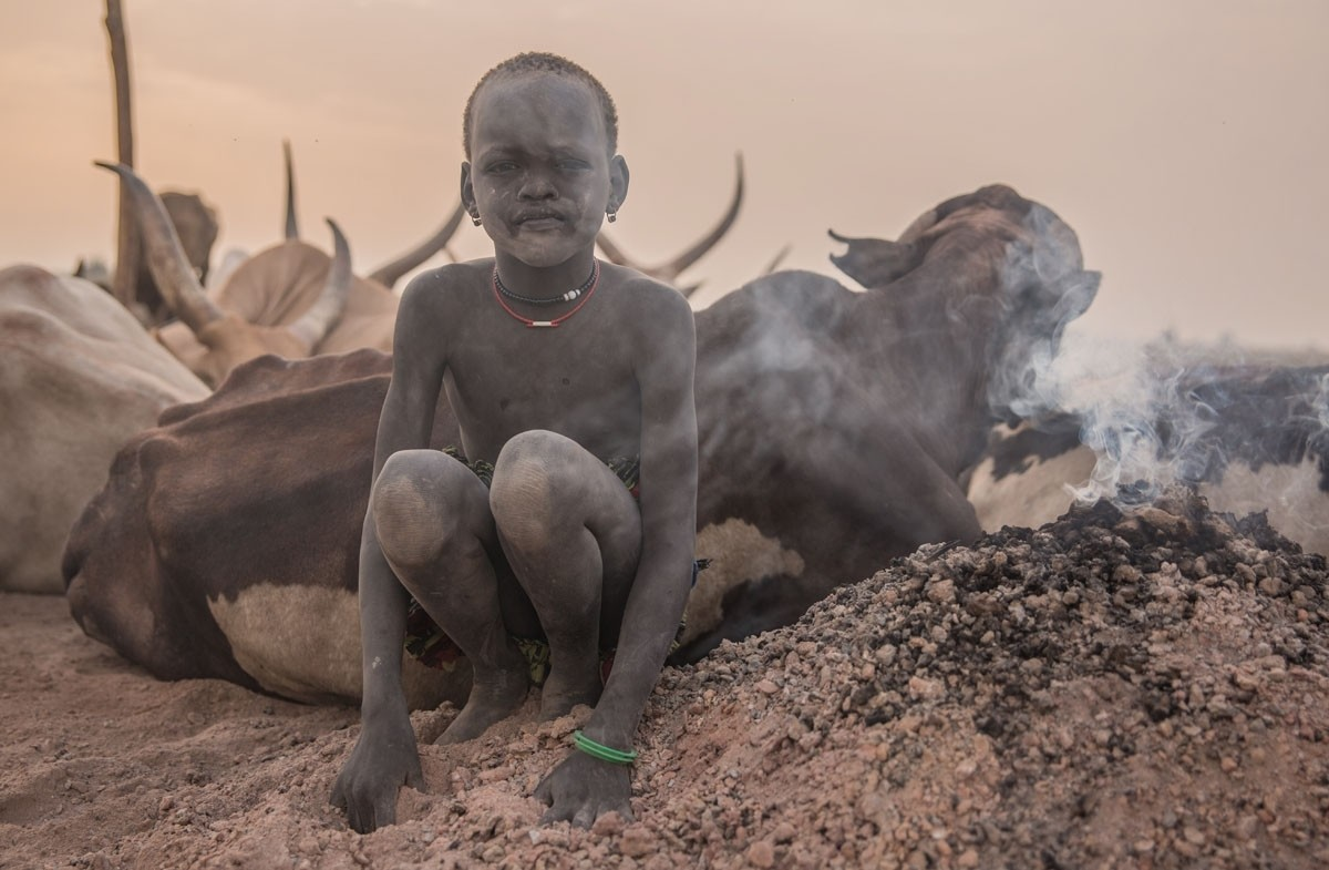 A boy uses white ash from burned cow dung as a mosquito repellent.