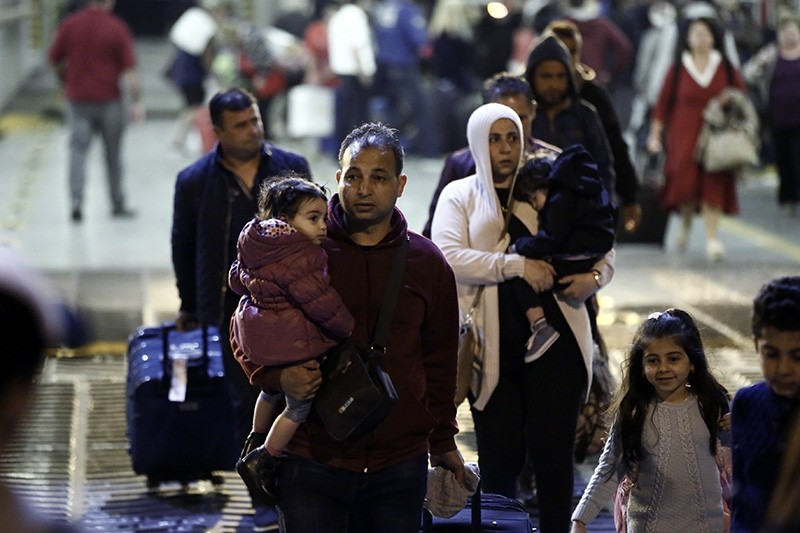 Refugees holding their children as they arrive with the 'Blue Star 2' passenger ship from the island of Samos, at the port of Piraeus, near Athens, Greece, 21 October 2017 (EPA Photo)