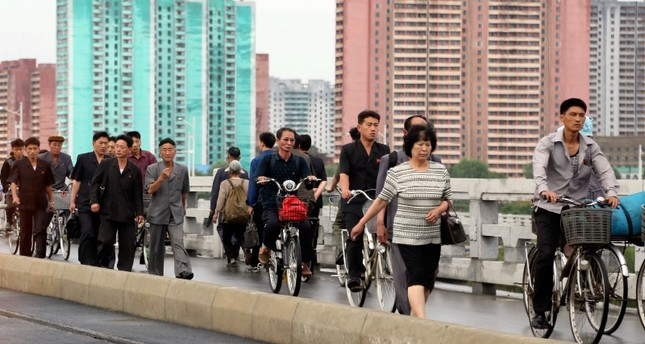 Men and women walk on a bridge as apartment buildings are seen in the background during the morning rush hour in Pyongyang, North Korea, Friday, June 15, 2018. AP Photo