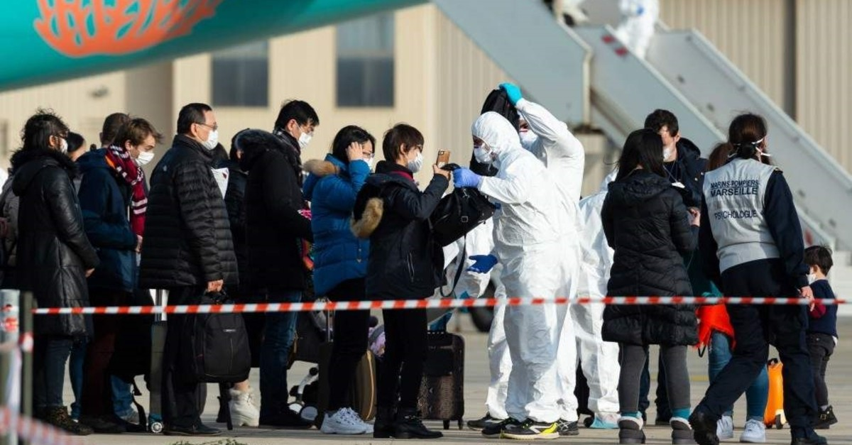 Passengers being checked as they disembark from a plane carrying French citizens flown out of the coronavirus hot-zone in Wuhan, upon their arrival at the Istres-Le Tube Air Base in Istres, southeastern France, Feb. 2, 2020. (AFP Photo)