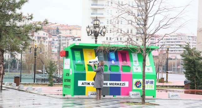 A woman dumps waste at a garbage collection point where different garbage is required to be dumped separately as part of zero waste project in Keçiören, Ankara, Feb. 13, 2019.