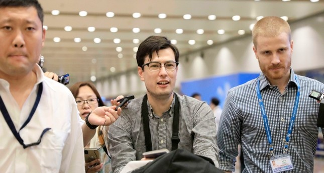 Australian student Alek Sigley smiles as he arrives at the airport in Beijing on Thursday, July 4, 2019. (Kyodo News via AP)