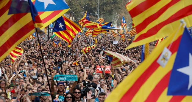 People gather as they watch on giant screens a plenary session outside the Catalan regional parliament in Barcelona, October 27, 2017. (REUTERS Photo)