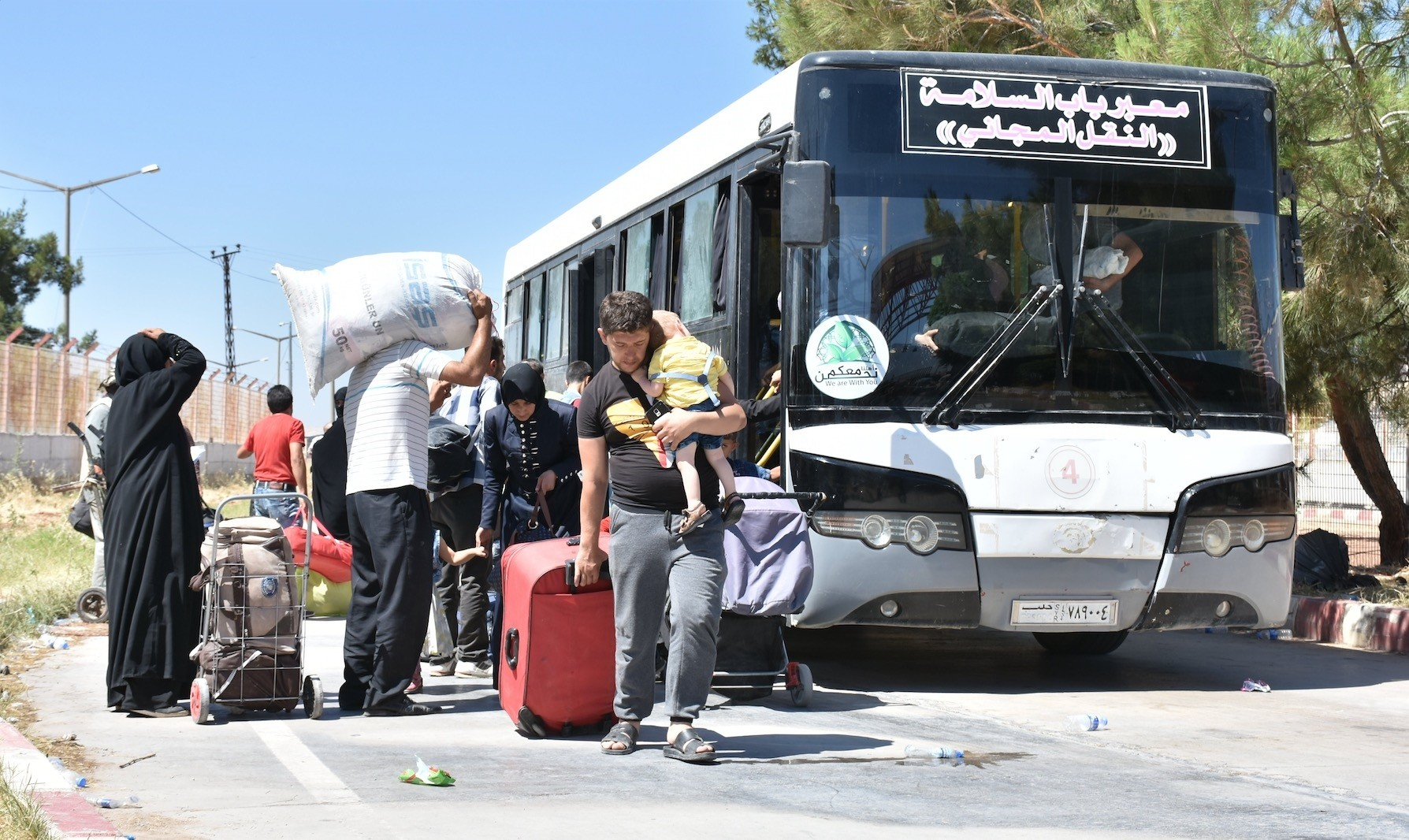 Syrians disembark buses at the u00d6ncu00fcpu0131nar border crossing.