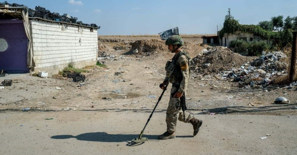 A Turkish soldier searches for mines as part of the security process to clear explosives planted by YPG militants in Tal Abyad, northern Syria.