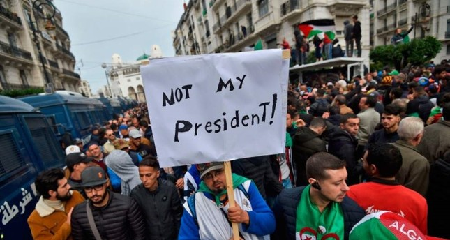 An Algerian protester lifts a placard in the capital Algiers on Dec. 13, 2019, as he takes part in a demonstration to reject the results of the presidential elections. AFP Photo