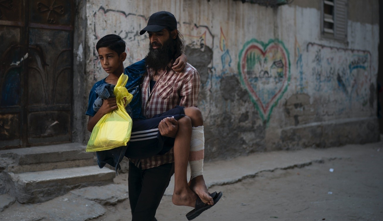 A Palestinian carries his 12-year-old son who was shot in the leg at one of the demonstrations on the  Gaza stripu2019s border with Israel, Sept. 16.