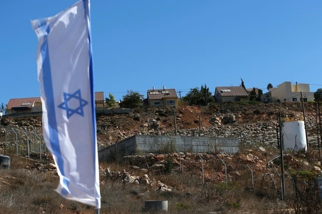 A picture taken on October 2, 2016 shows an Israeli national flag flying next to an Israeli building site of new housing units in the Jewish settlement of Shilo in the illegally occupied Palestinian West Bank. (AFP Photo)
