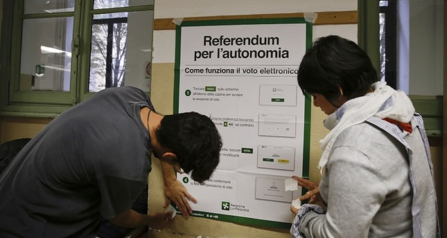Scrutineers fix a poster at the Berchet School polling station, in Milan, Italy, Saturday, Oct. 21, 2017. (AP Photo)