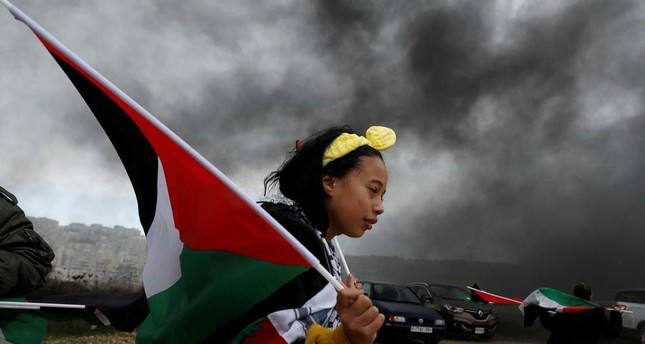 A girl holds a Palestinian flag during a protest against U.S. President Donald Trump's Middle East peace plan, in the village of Bilin in the Israeli-occupied West Bank, Feb. 7, 2020. REUTERS Photo